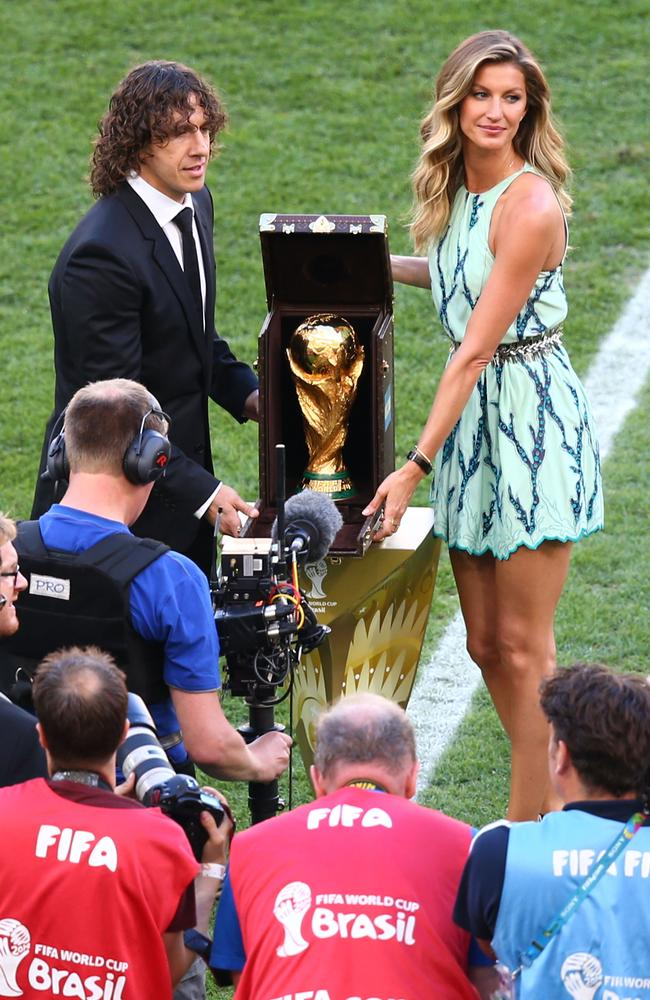 Puyol and Bundchen unveil the trophy.