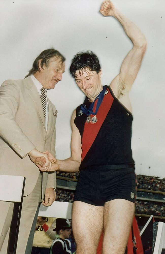 Essendon ruckman Simon Madden, receiving the Norm Smith Medal after the 1985 Grand Final, has been included the in the rebooted AFL Team of the Century.