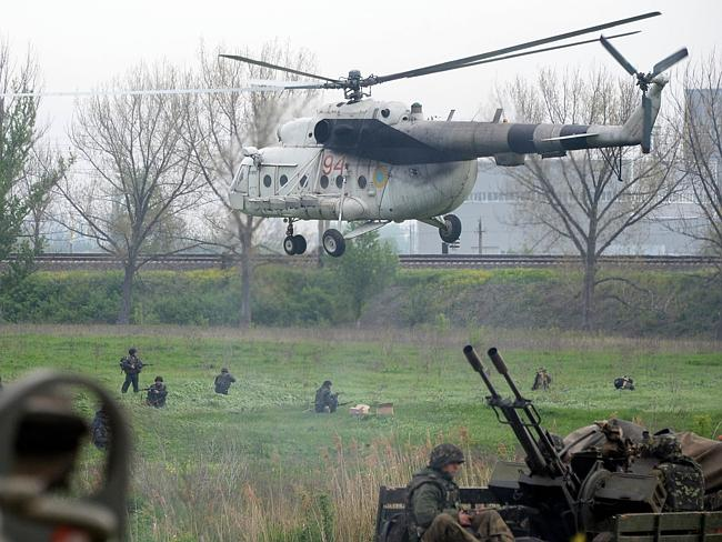 Full combat mode ... Ukrainian soldiers arrive to reinforce a checkpoint which troops seized in the early morning in the village of Andreevka, as Ukraine's military lost two helicopters and two servicemen. Picture: VASILY MAXIMOV