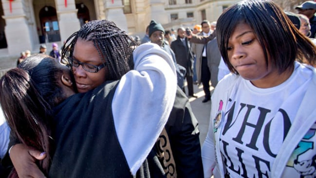 Battle for justice ... Jacquelyn Johnson, second from left, the mother of Kendrick Johnson, is embraced by Monique Mosely, left, as Johnson's daughter Kenyetta, right, stands by following a rally.