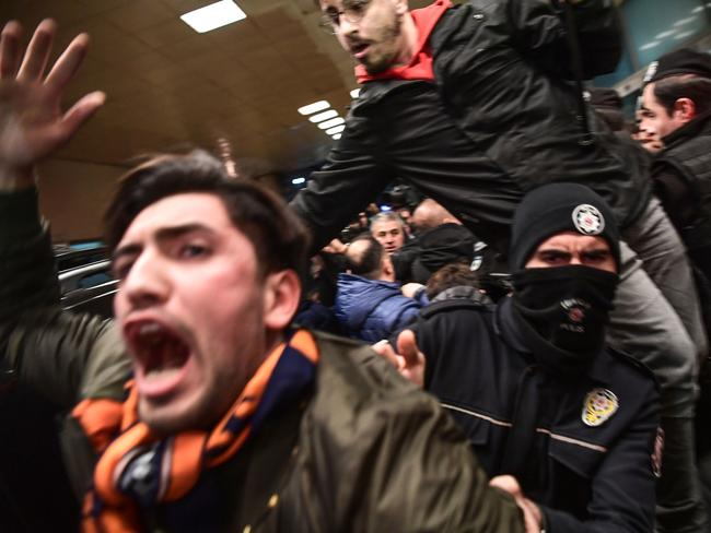 Turkish anti-riot police officers push back Basaksehir supporters.