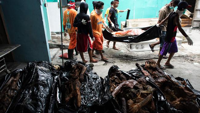 Workers carrying cadavers in various stages of decomposition at the morgue of Henry's Funeral Homes in Manila, October 2016. Picture: AFP / Noel Celis.