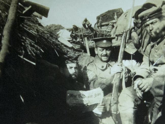In this photo provided by the family of German soldier, Kurt Zehmisch, a German soldier wears the hat of a British soldier as he sits in a trench with other German soldiers. Picture: AP/In Flanders Fields Museum/Virginia Mayo
