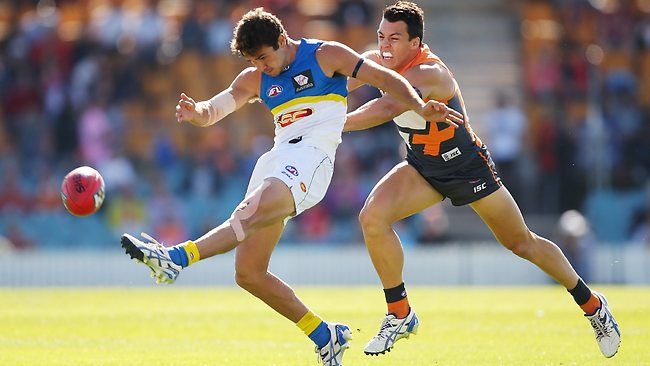 Jarrod Harbrow of the Suns gets a kick away under pressure from Dylan Shiel.