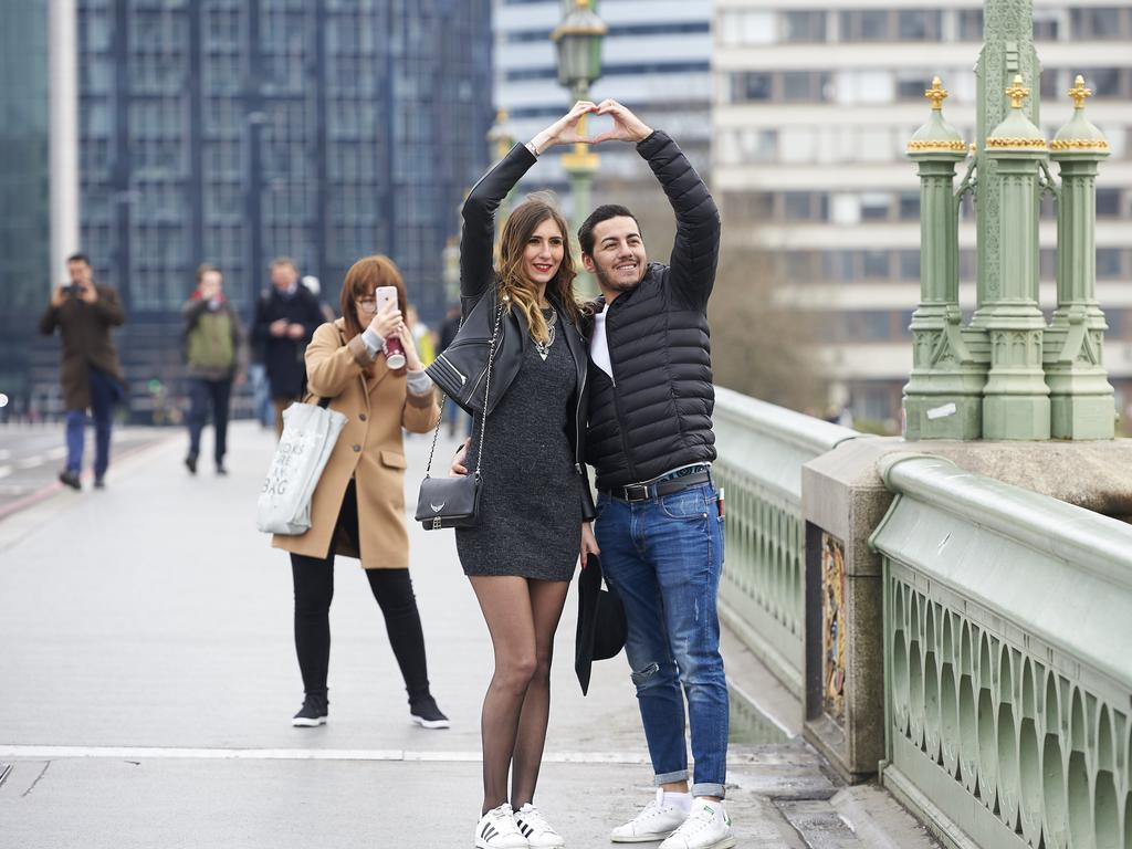 People pose for photographs on Westminster Bridge in central London on March 23, 2017 after the bridge reopened to traffic following its closure during the March 22 terror attack. Picture: AFP