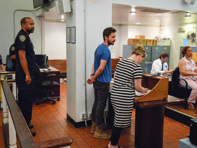 Disruptive ... Shia LaBeouf, centre, represented by a Legal Aid lawyer, is arraigned in Midtown Community Court, in New York. Picture: Anthony DelMundo
