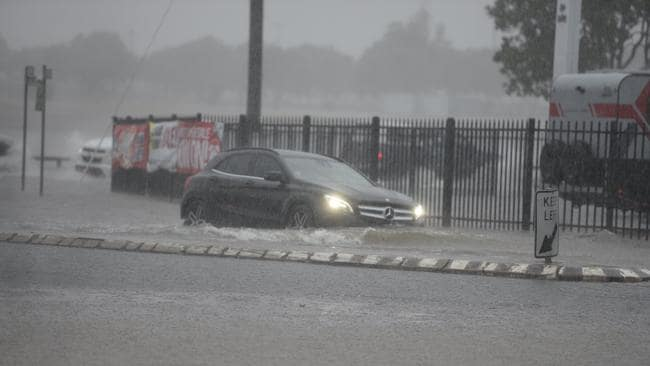 A Mercedes tries to get through flooded water in Bundaberg.
