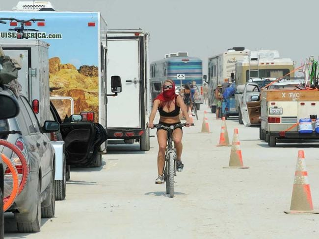 A woman rides her bike between cars waiting to enter Burning Man. Picture: AP