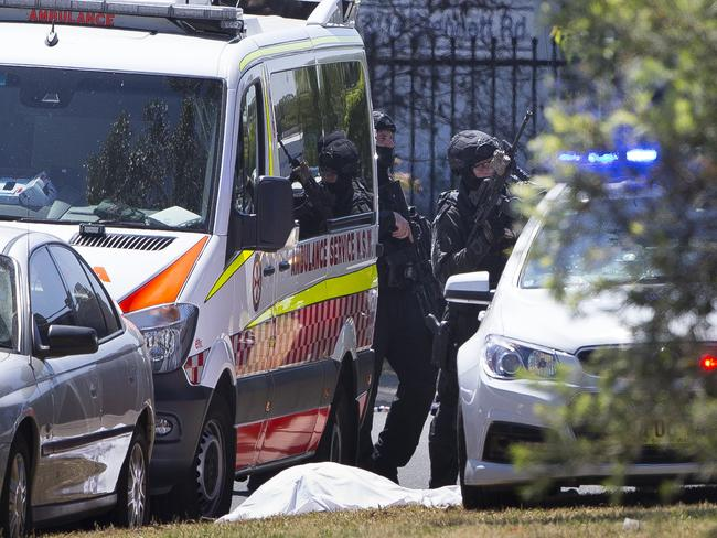 A body can be seen covered in a white sheet as police move into position. Picture: Melvyn Knipe