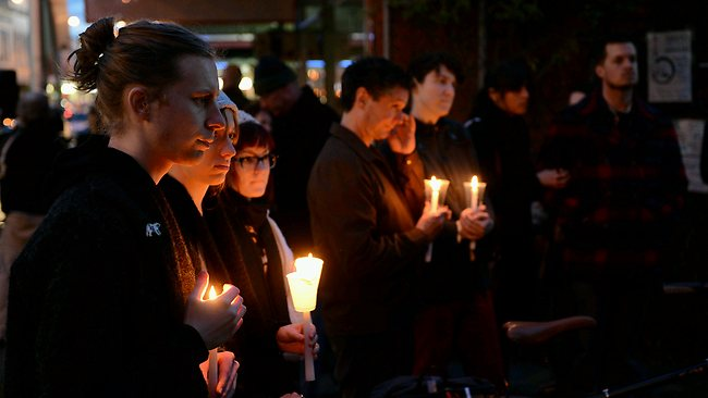 Mourners gather last night outside nearby Baptist Church. Picture: Eugene Hyland