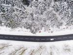 This aerial view taken on February 26, 2018 with a drone shows a car driving on a country road through a winter snowy forest in the district of Holzminden, Germany. Picture: AFP PHOTO / dpa / Julian Stratenschulte