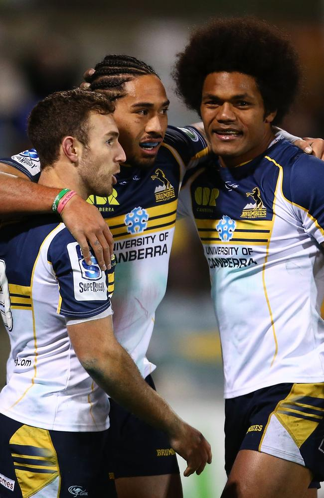 Brumbies players celebrate a try by Joe Tomane (centre).