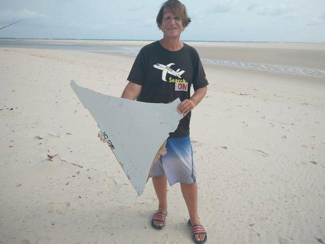 Blaine Gibson with the suspected aircraft horizontal stabiliser, which is being investigated for links to MH370, near where he found the object. The words 'NO STEP' can clearly be seen along one edge.
