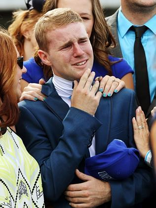 Nathan's twin brother Tommy is comforted by family during a tribute to the jockey who died last week.