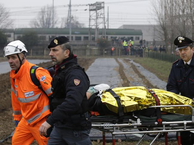 An injured passenger is taken away on a stretcher after a train, seen in the background, derailed in northern Italy. Picture: AP/Luca Bruno