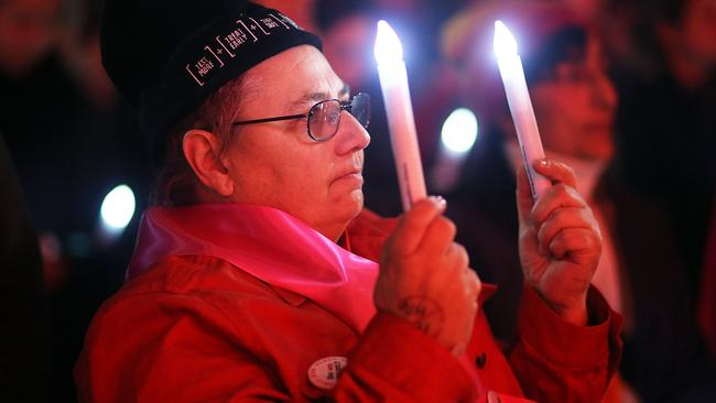 Members of the public hold candles to mourn the victims of HIV/AIDS and the victims of flight MH17 during a candlelight vigil at Federation Square.