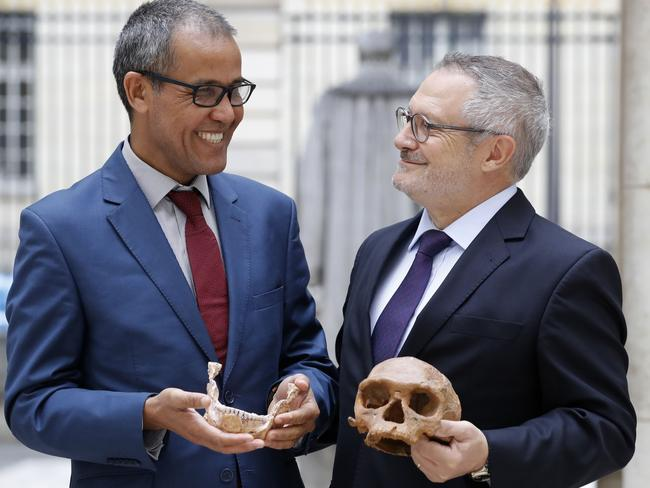 French palaeoanthropologist Jean-Jacques Hublin (R) and Abdelouahed Ben-Ncer of the National Institute of Archaeology and Heritage Sciences in Morocco pose with the casting of a skull of Homo Sapiens discovered in Morocco on June 6, 2017 in Paris. Picture: Patrick Kovarik