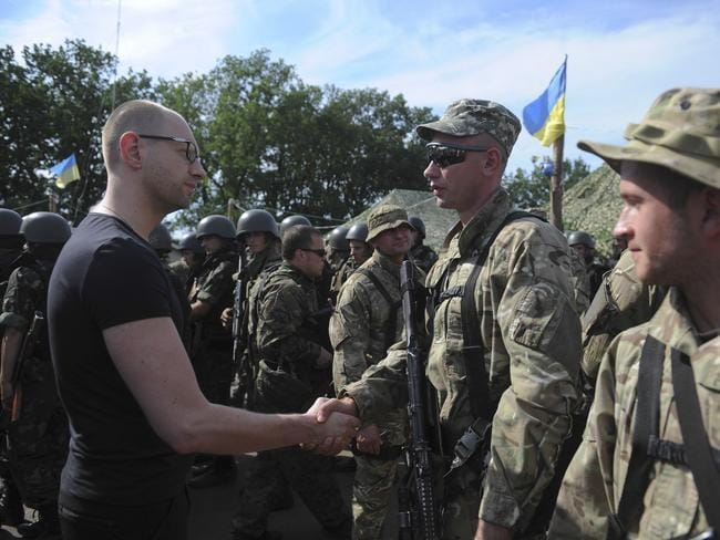 Resigning ... Ukrainian Prime Minister Arseniy Yatsenyuk, left, greets a soldier during inspection of a Ukrainian Army position outside the eastern town of Slovyansk, Ukraine.