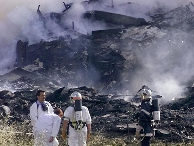 Rescue workers stand near the debris of the hotel on which an Air France Concorde en route to New York crashed in Gonesse, outside Paris shortly after take off. Picture: Laurent Rebours.
