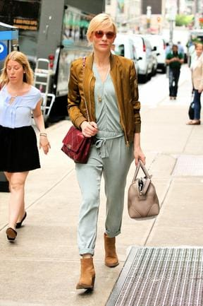 Australian actress Cate Blanchett, wearing a light green jumpsuit, gold silk jacket, brown suede ankle boots, and carrying maroon and grey handbags. Splash
