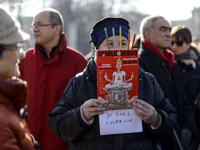 A woman holds a copy of Charlie Hebdo during a gathering in the center of Geneva on January 8. Picture: Fabrice Coffrini.