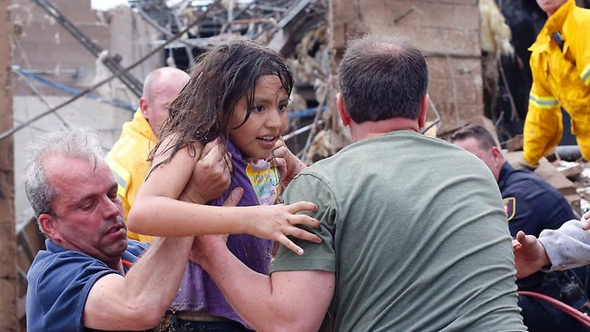 Oklahoma tornados: a child is pulled from the rubble of the Plaza Towers Elementary School in Moore, Oklahoma, and passed along to rescuers after a tornado as much as 1.6km wide with winds up to 320 kph roared through the Oklahoma City suburbs, flattening entire neighborhoods, setting buildings on fire and landing a direct blow on an elementary school. Photo: AP/Sue Ogrocki