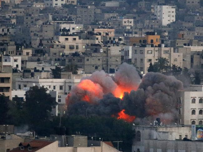 Sudden impact ... Flames erupt from a building hit by an Israeli air strike in Gaza City. Israeli warplanes have been pounding the city in a major new confrontation with Palestinian militants, as Hamas flexed its firepower and sent thousands running for shelters across the country.