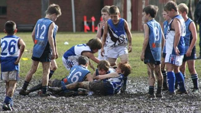Young footballers play in the mud at Webb Oval, Glenunga.