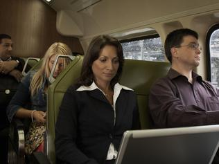 Businesswoman travelling on train using laptop