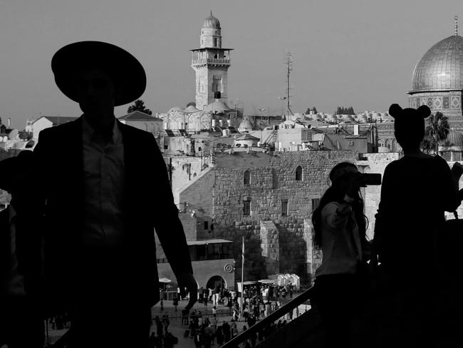 An Ultra-Orthodox Jewish man stands with tourists at the Jewish quarter in Jerusalem's Old City overlooking the Dome of the Rock mosque. Picture: AFP