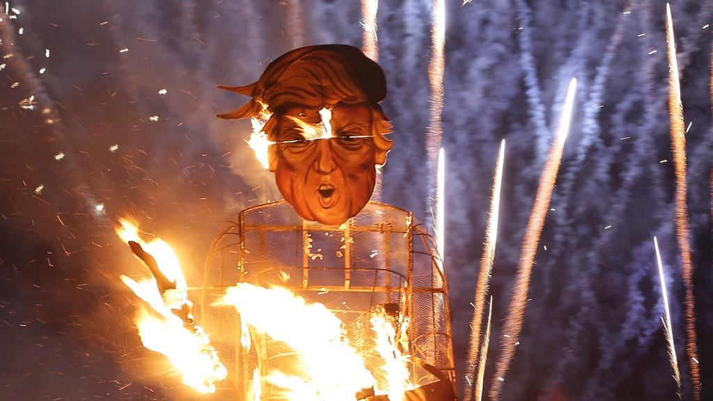 Fireworks explode as flames engulf an effigy of Donald Trump. Picture: AFP