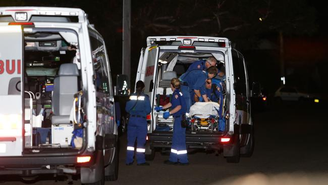 Ambulance paramedics attend to a stabbed man. Picture: Bill Hearne