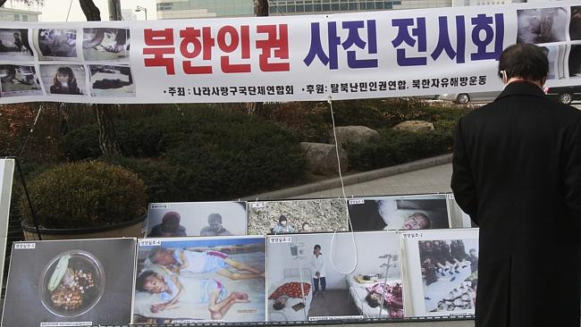 "Suffering...A South Korean man looks at photos of starving North Korean children at an exhibition in Seoul. The banner reads: ""North Korea's food crisis, North Korean human right's photo exhibition."" Picture: AP Photo/Ahn Young-joon)"