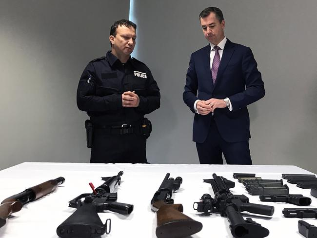 Justice Minister Michael Keenan examines a range of weapons after announcing a new national gun amnesty. Picture: AAP