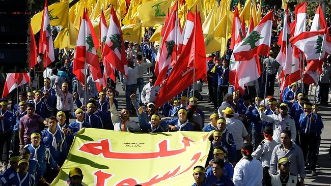 "Hezbollah supporters wave a flag in Arabic that reads: ""messenger of Allah,"" as they take part in a protest in Lebanon's eastern city of Baalbek. Anger over insults to Islam's Prophet Muhammad isn't enough to bring Lebanon's divided Sunni and Shiite Muslims together. (AP Photo/Bilal Hussein)"