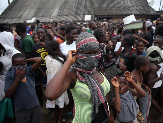 Break-in ... a mob enters the grounds of an Ebola isolation centre in the West Point slum in Monrovia.