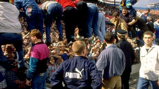 Desperate efforts ... fans tried to haul others over the fence to safety on the pitch side.