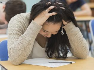 Stressed student sitting in a classroom at a table while doing a test
