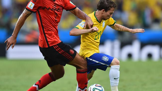 Bernard of Brazil fights off Francisco Javier Rodriguez of Mexico.