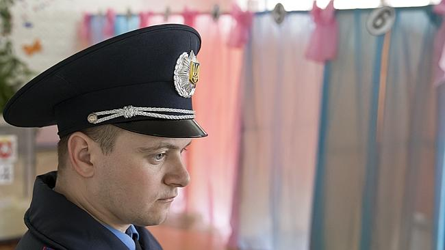 Watching ... A Ukrainian policeman supervises activity in a voting station in Perevalne, Ukraine. Picture: AP