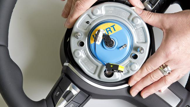 A worker demonstrates a pyroelectric wheel airbag initiator during a presentation for journalists at Takata in 2014. Picture: AP