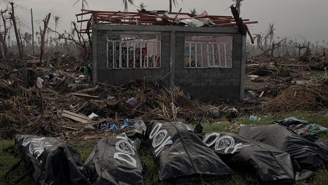 The bodies of five victims of typhoon Haiyan lie in front of a house damaged after five-metre waves swept across low-lying islands. Picture: AFP/ Nicolas Asgouri.