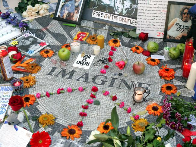 Lennon tribute ... fans memorialised their hero at the 'Imagine' mosaic in the Strawberry Fields section of New York's Central Park on the 25th anniversary of his death. Picture: Mary Altaffer