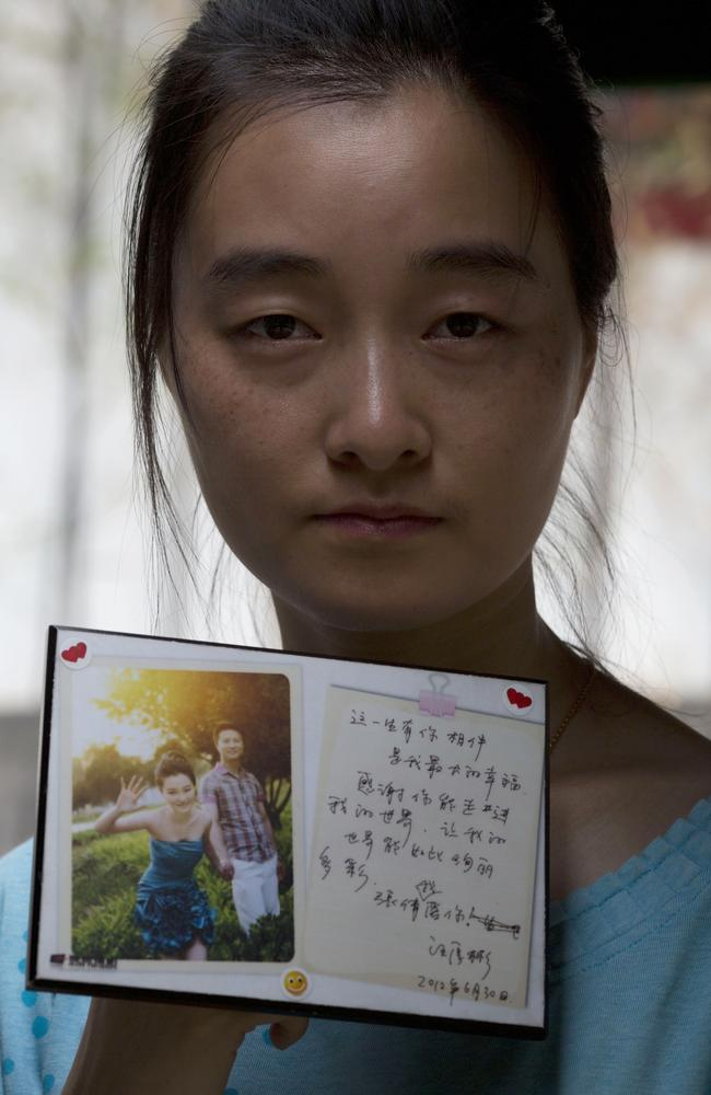 No trace ... Zhang Qian holds up a photo taken with her husband, Wang Houbin, 28, with a love letter written by him. Wang was on board the missing Malaysia Airlines Flight 370.