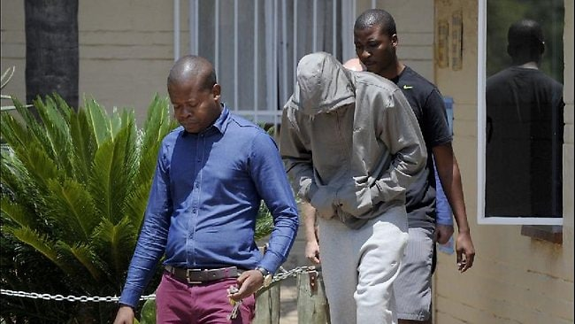 South Africa's Olympic sprinter Oscar Pistorius (C) leaves the Boshkop police station on February 14, 2013 in Pretoria East, to be taken into police custody after allegedly shooting dead his model girlfriend having mistaken her for an intruder at his upscale home. AFP PHOTO
