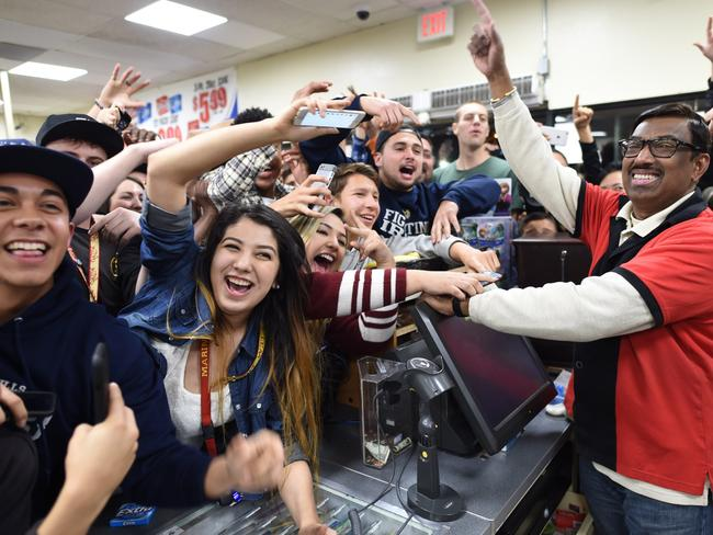 Winner ... 7-Eleven store clerk M. Faroqui celebrates with customers after learning the store sold a winning Powerball ticket. Picture: AP