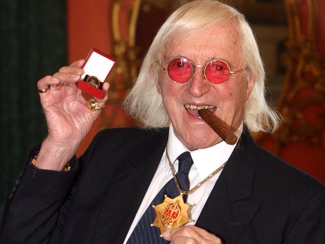 Honoured ... Jimmy Savile holding a medal in London.