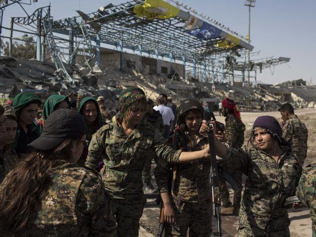 Members of the US-backed Syrian Democratic Forces (SDF) celebrate at stadium that was the site of Islamic State fighters' last stand in the city of Raqqa. Picture: Asmaa Waguih