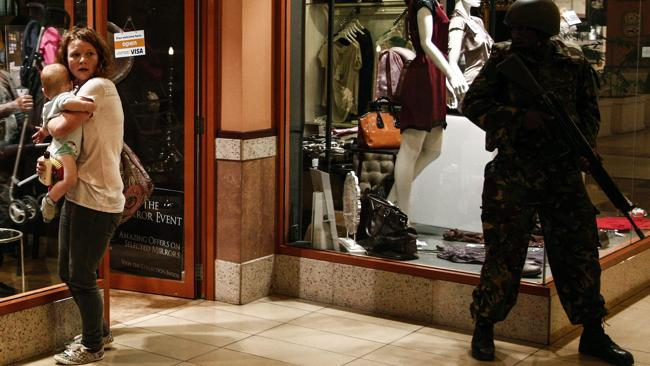 A woman shields a baby as a soldier stands guard inside the Westgate shopping mall after the shootout.