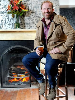 Owner of the King's Head hotel, Gareth Lewis, warms up by the fire. Picture: Keryn Stevens.